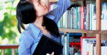 nastolatka-przy-regale-sięgająca-po-książkę